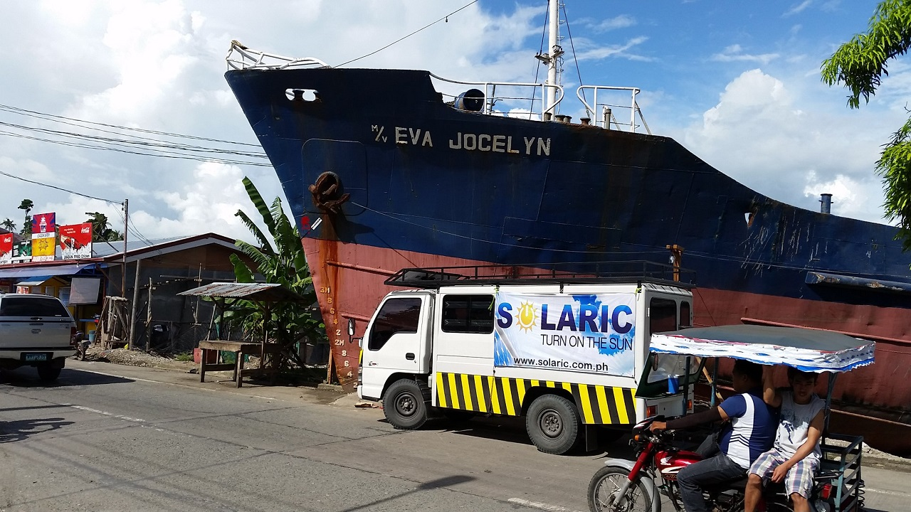 A Solaric van parked in front of a ship that has grounded on to land