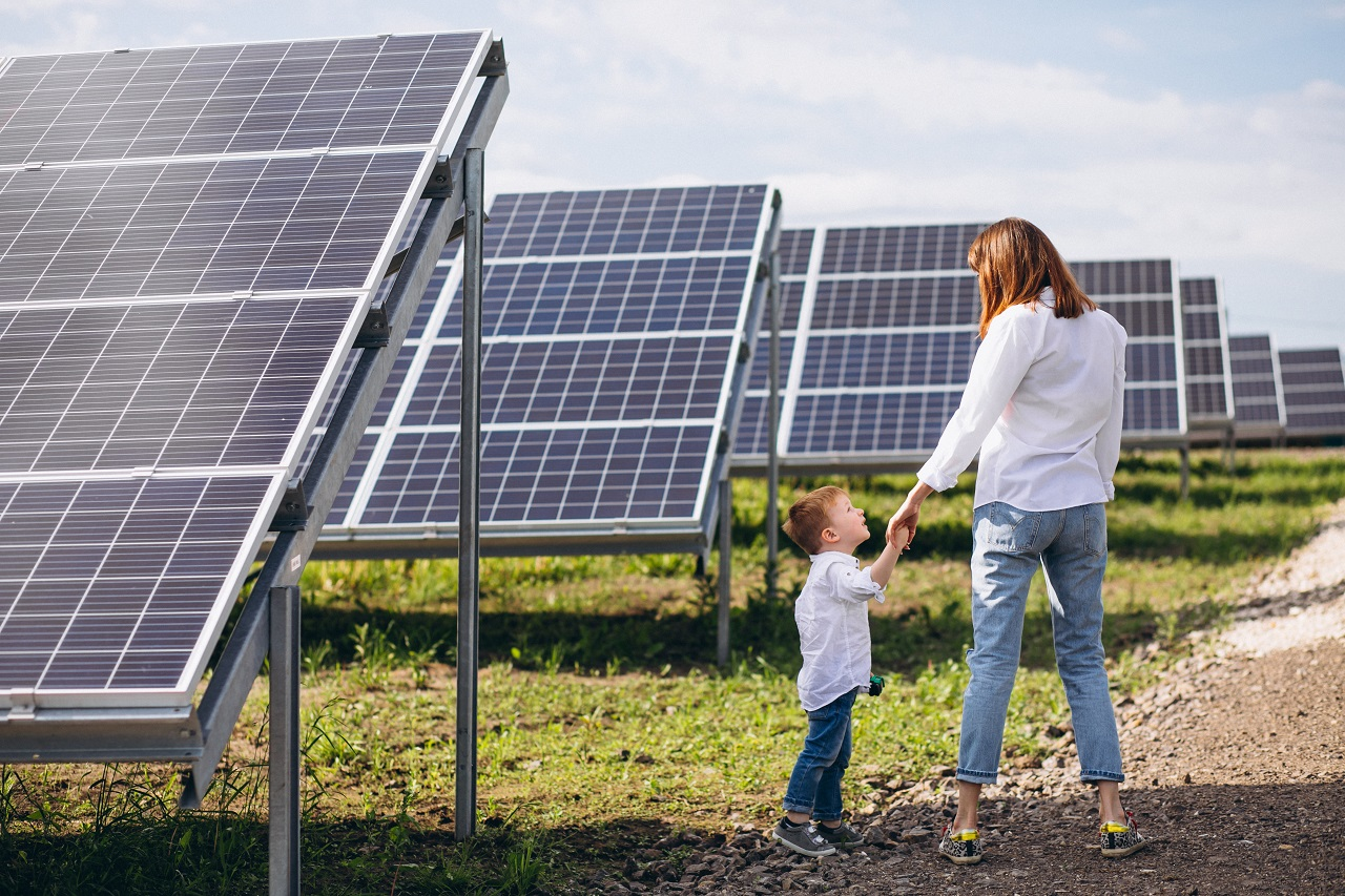 Mom and young son standing beside solar panels
