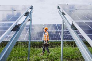A repair man walking in between solar panels