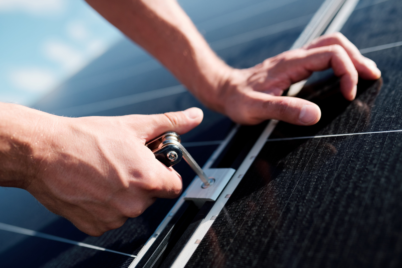 A solar technician's hands screwing a bolt into a solar panel