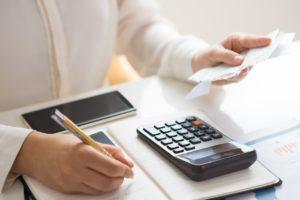 A woman computing her bills