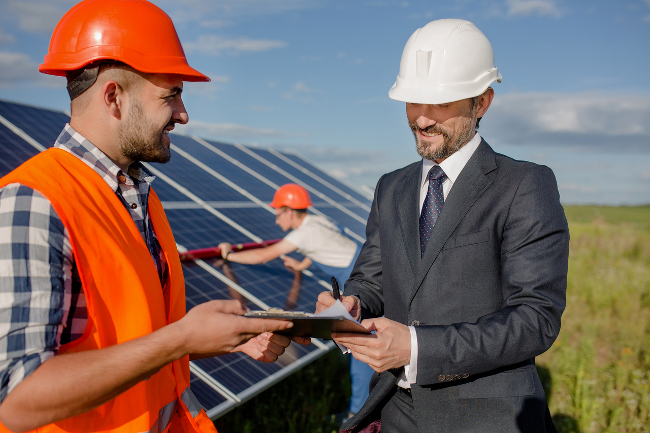 Two men shaking hands in front of a solar panel