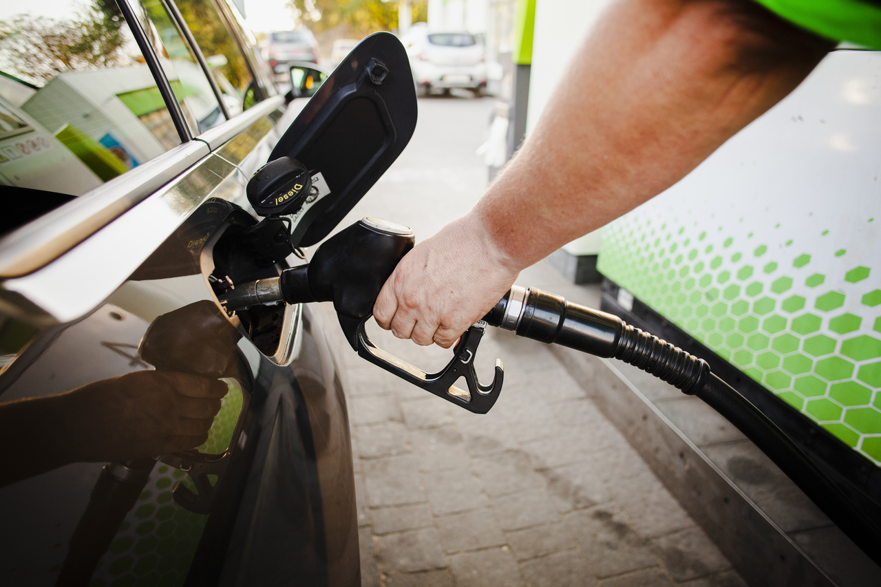 Close up of a hand putting gas in their car