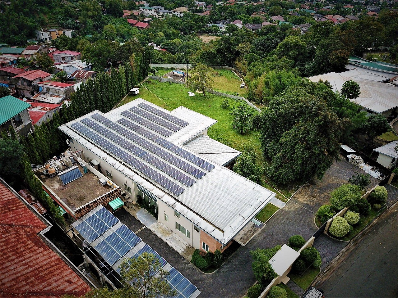 Top wide view of a white roof filled with solar panel systems