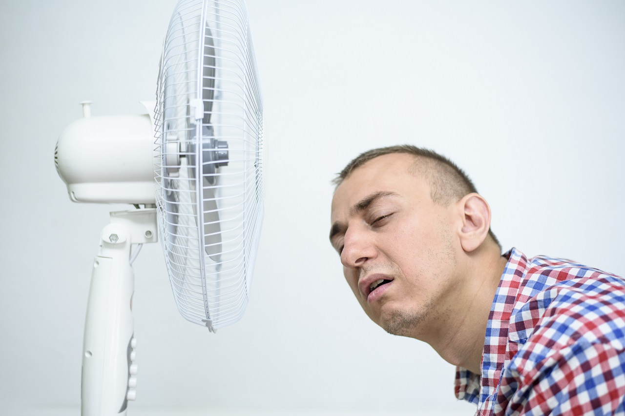 A man near a fan due to the extreme heat
