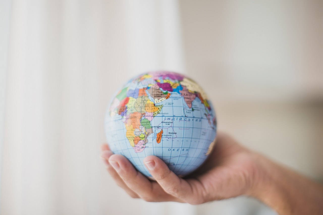A hand holding a globe