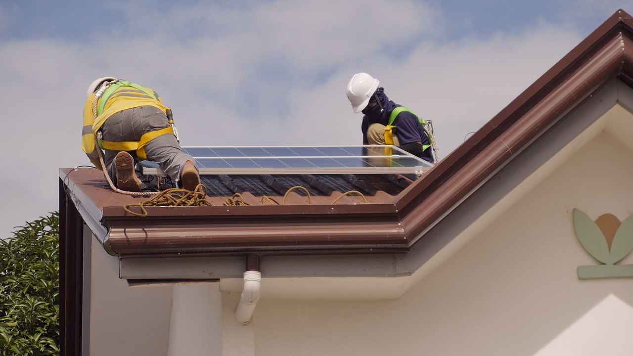 Solaric workers installing a rooftop solar panel