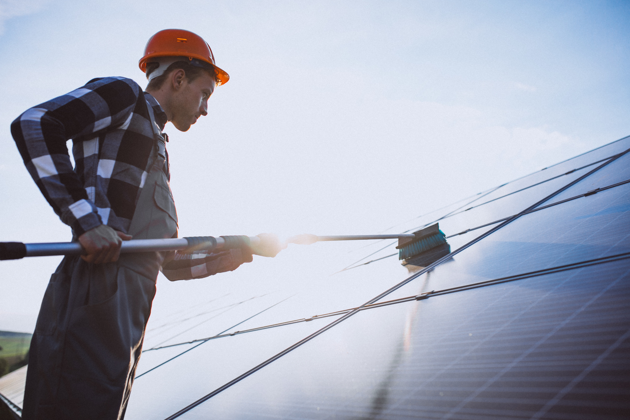 A worker cleaning a solar panel