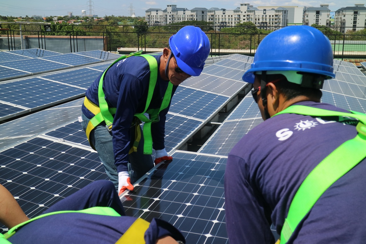 Solaric installers on a rooftop
