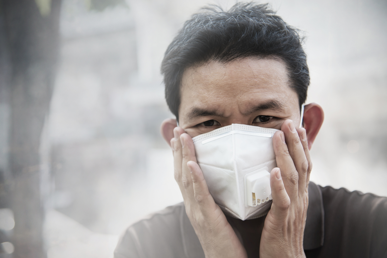 A man wearing a face mask breathing in dusty air