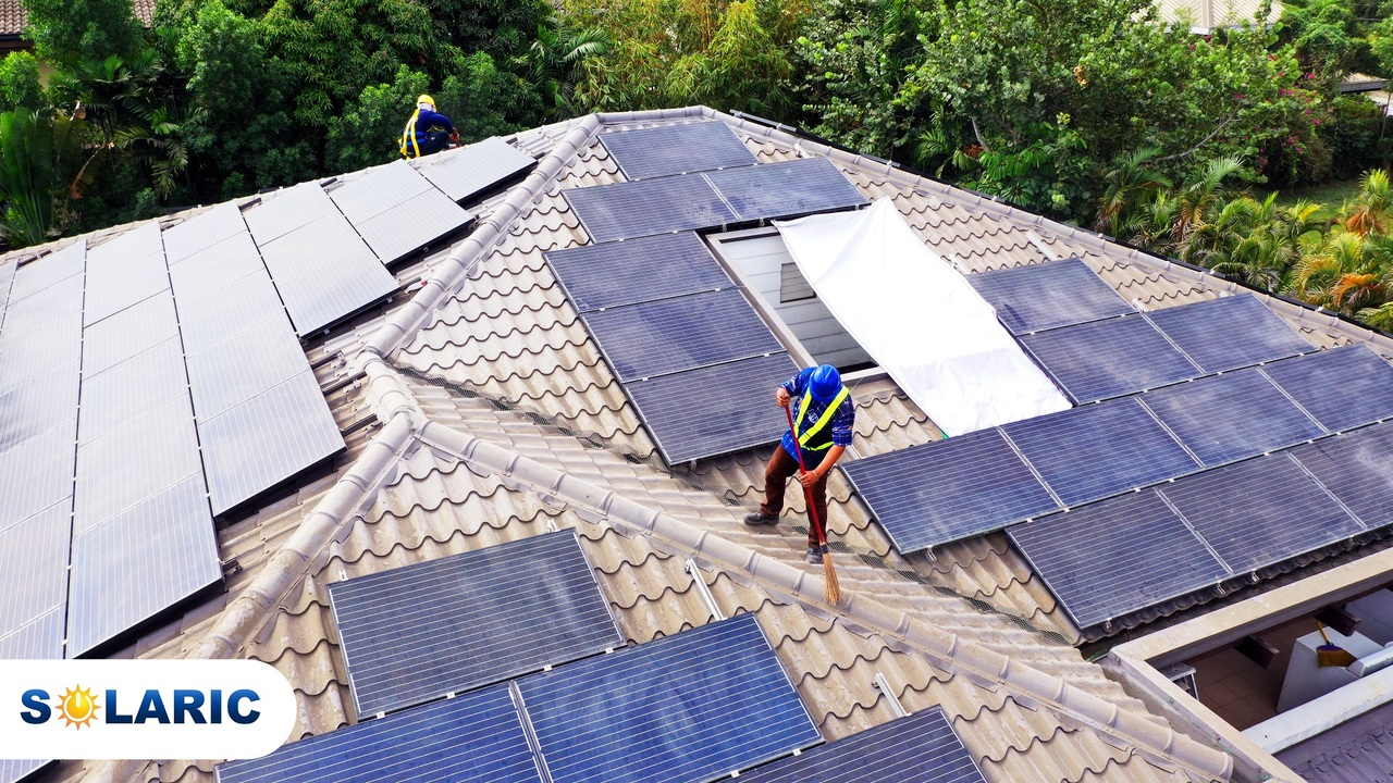 Two Solaric employees cleaning solar panels on a rooftop