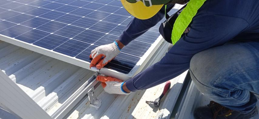 A professional solar installer installing solar grids to a roof