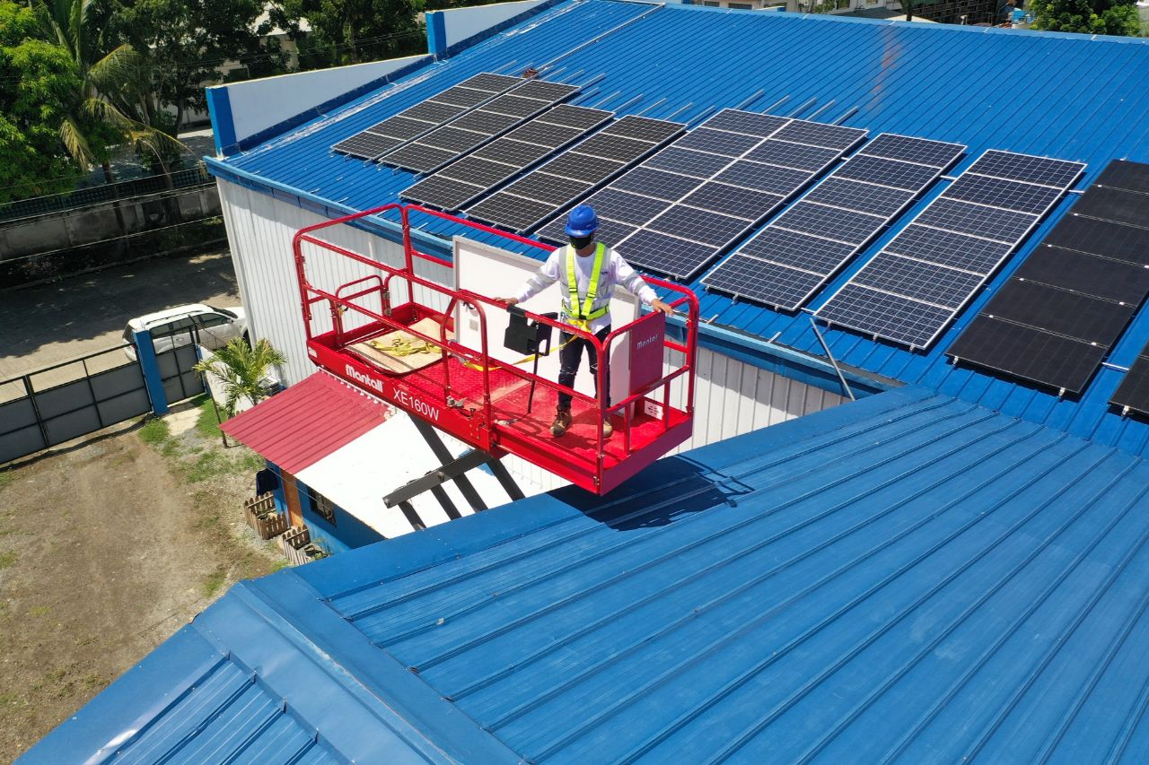 Man on a boom lift about to install solar panels